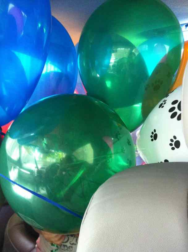 bunch of colorful balloons smashed together. Hint of a car seat below them.