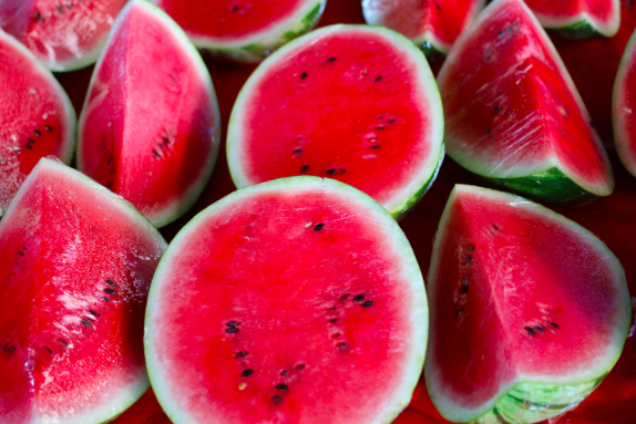 photo of cut open watermelons, showing their red insides and the occasional black seed