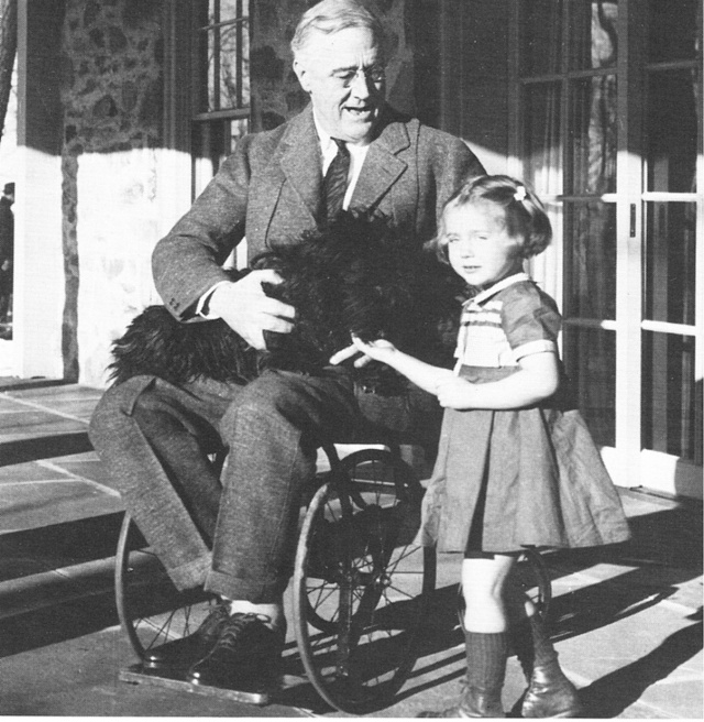 A wheel-chair bound FDR holds a dog in his lap and interacts with his granddaughter.