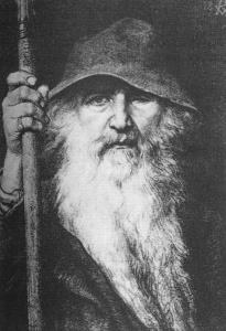 Black and white image of an old man with one missing eye wearing a floppy hat, holding a cane, and sporting an immensely long white beard.