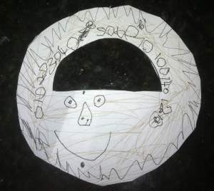 A paper medallion, with hand drawn preschooler designs on it, and fat numbers to measure the angles.