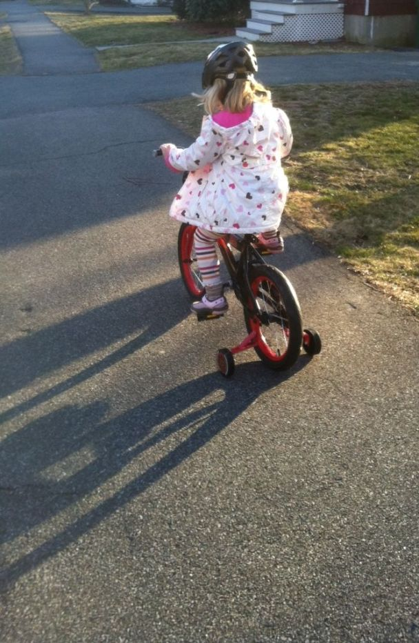 A four-year-old girl in a polka dot jacket peddles down the sidewalk on a tiny red bike with training wheels.