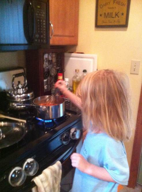 The four-year-old stirs the ketchup on the stove.