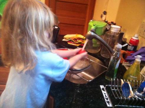 The four-year-old washes the tomatoes in the sink.