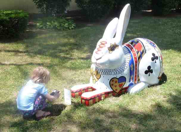 a five-year-old girl crouches to take a picture of a giant rabbit's feet.