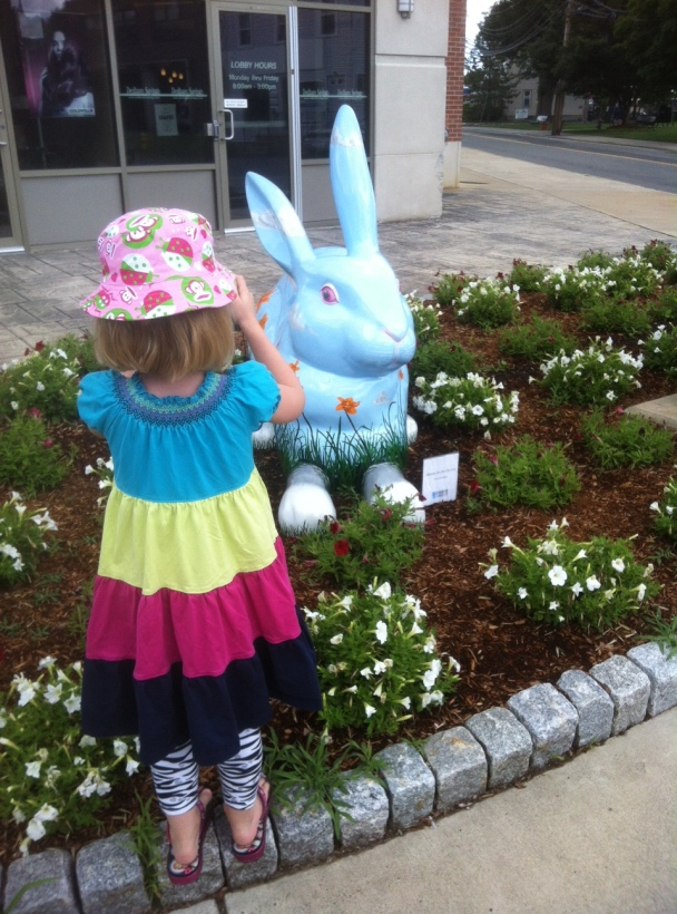 A young girl takes a picture of a giant blue rabbit.