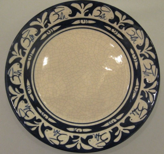 Dedham Pottery was famous for its off-white, crackled glaze plateware with a bright band of blue and white figures around the edge.