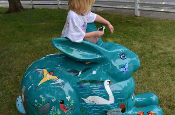 The Five-Year-Old sits on top of a teal-colored bunny painted all over with birds and flowers.