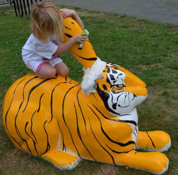 A five year old girl sits on the back of a giant tiger-striped rabbit, hugging its remaining ear. The other ear has been lopped off and a gauze bandage applied to its stump.