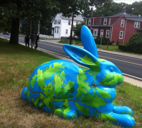 Avery Oak sits on a lawn. The blue bunny is covered with a network of oak tree branches, leaves, and acorns.