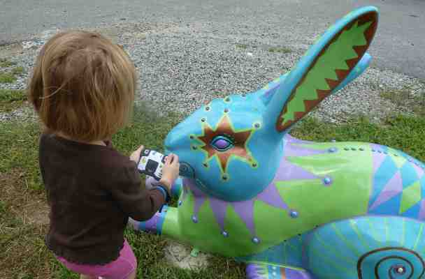 A five-year-old crouches slightly as she takes a picture of a giant rabbit's eye.