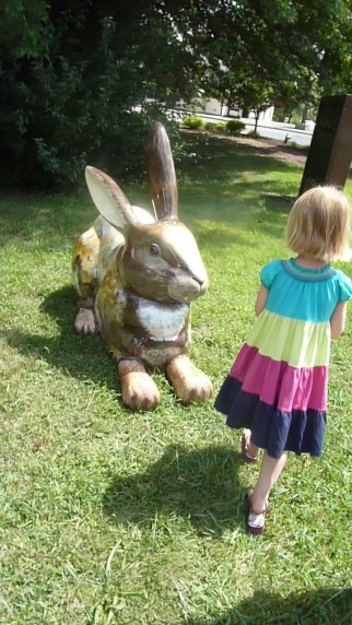 A five year old girl stands in a park facing a large brown painted rabbit.