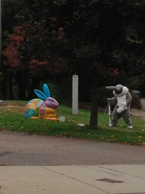 a person in a bunny suit sets up a camera on a tripod across from Lisa Houck's Spiral Bunny.