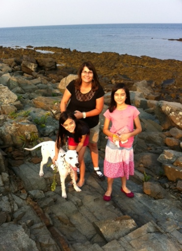 Cathy, her two daughters, and their dog Trooper stand on a rocky beach.