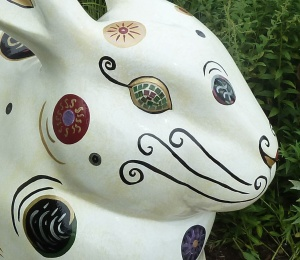 Close-up of the rabbit's face, with its swirly mustache-like whiskers and perfectly round circles.