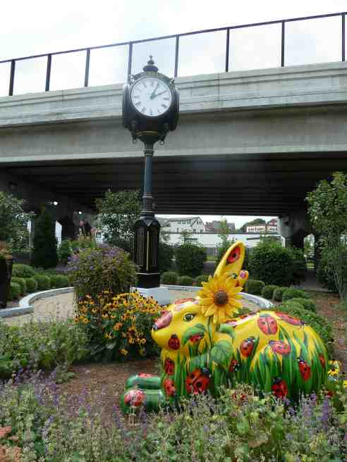 This photo shows Lady Bugs Bunny sitting in a small garden under the overpass at Dedham Crossing in Dedham Massachusetts.