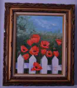 The painting shows red poppies behind a white picket fence.