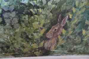 A close-up of a mural showing the same brown rabbit from the previous picture, this time hiding in a green bush.
