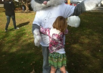A small girl hugs a person in a giant rabbit suit.