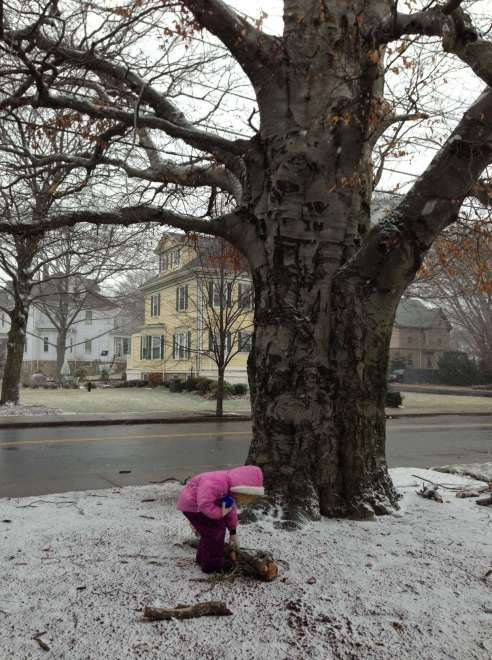 A girl bends over a branch on the ground. There is almost no snow to be seen.