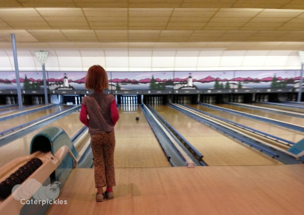 A six-year-old girl watches her bowling ball roll down a candlepin lane.