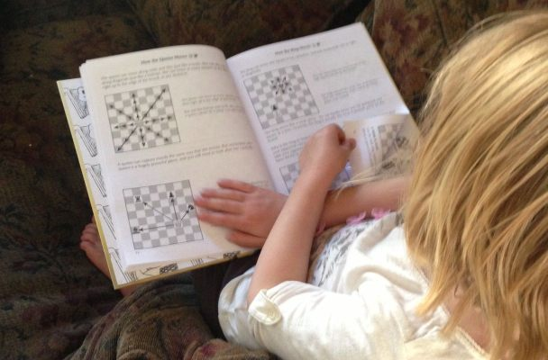A six-year-old girl reads a book on how to play chess.