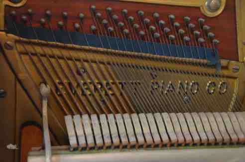 Closup of a portion of the pin block in my Everett, showing the transition from copper to steel strings. Incidentally, my piano uses an exposed pin block, an older style of construction. In newer models, the metal harp covers the pin block and has a series of holes through which piano tuners access the pins. (Photo: Shala Howell)