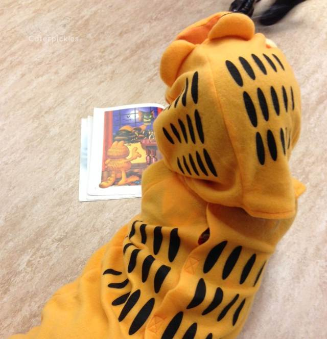 The Six-Year-Old camped out on the floor at school, waiting for the Halloween parade to start. Why yes, that is a Garfield book. (Photo: Shala Howell)