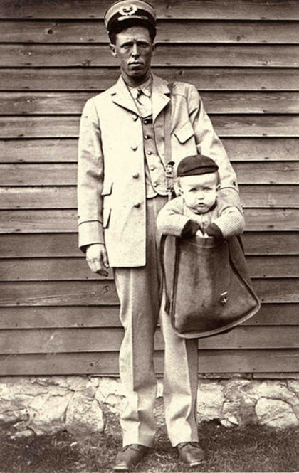 """A mail carrier poses with a child in his mailbag for a photograph illustrating the new regulations against shipping children parcel post. Although kids generally fell under the 50 lbs guideline for parcel post, the Postmaster General determined that children did not fall under the """"bugs and bees"""" classification that limited the types of fauna that could be sent through the US mail. (Photo & background info on it via the Smithsonian's public domain Flickr stream.)"""