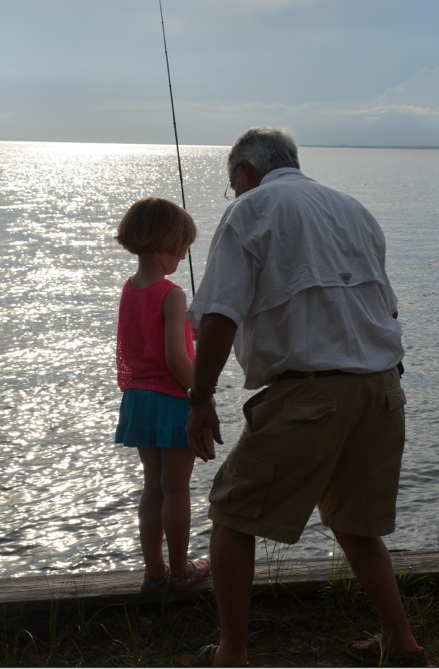 A grandfather teaches an eight-year-old girl how to hold a fishing rod.