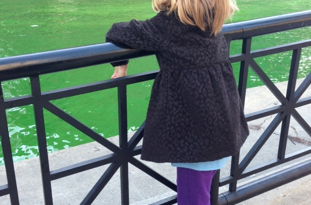 My daughter stands at a black gate overlooking the temporarily bright green Chicago River.