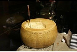 A wheel of Grana Padano cheese with a cheese knife sticking out of its top.