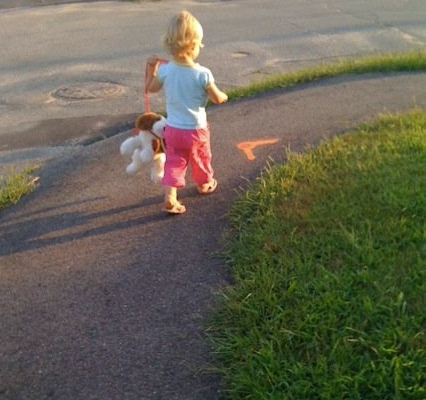 My daughter, then only two, takes her stuffed dog for a walk outside. The dog is hanging from a leash, lifted up just enough to keep from dragging on the ground.