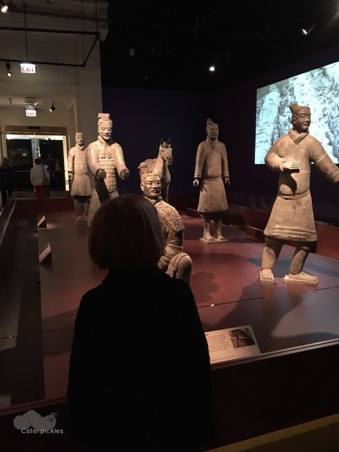 A nine-year-old girl (seen from the back) looks at a collection of Terracotta Warriors.