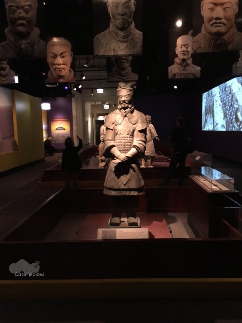 In the foreground, stands the general of the terra cotta army. Behind him, you can see in shadow a little girl saluting his troops.