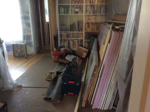 View of construction materials (sheet rock, tools, etc.) piled along the walls of what used to be my office.