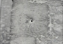 The medieval sundial looks like a hole in a stone wall surrounded by scratches in a circle at regular intervals.