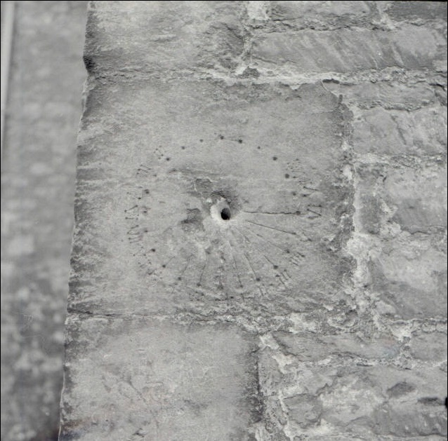 Medieval sundial etched into the side of St. Mary's Church in Bilbury, Gloucestershire. This dial is missing its gnomon, the bit that creates the shadow based on the position of the sun. Even with it, though, it wouldn't have been a ton of help. (Photo: Alan Longbottom)