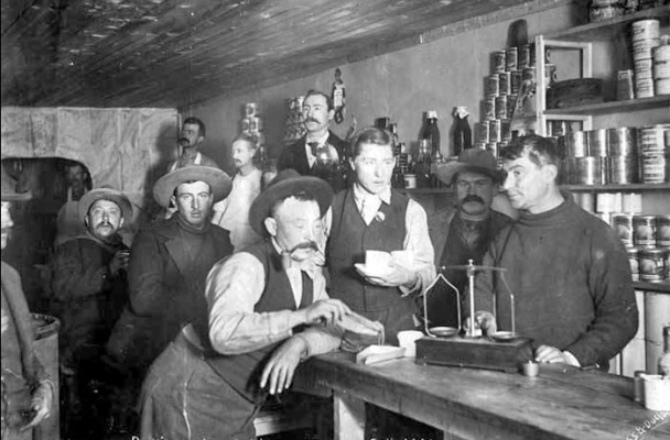 In this black and white photo, miners wait as the store manager weighs out their gold dust.