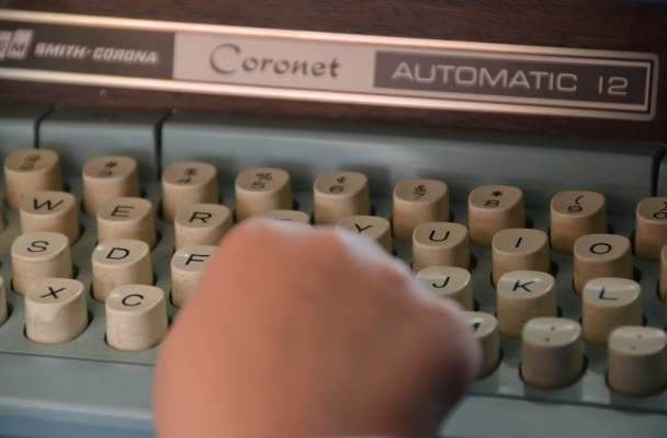 a child's hands pecks at the keys of an old Smith-Corona Coronet typewriter.