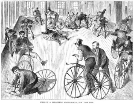 "Scene from a bicycle school in New York City, back in the days when bicycles were still called ""velocipedes."" (Public domain.)"