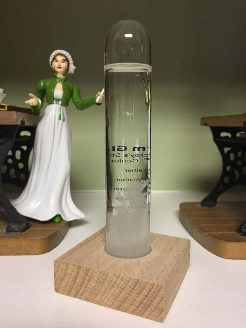 Photo of a Jane Austen action figure posed on a bookshelf next to the no longer working storm glass.
