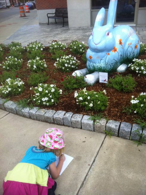 a girl in a spring dress and a fun ladybug sun hat lies on the sidewalk in front of a giant blue rabbit. She's clearly sketching it.