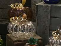 Clear glass pumpkins with gold leaves and steams sit on wooden crates in an outdoor display