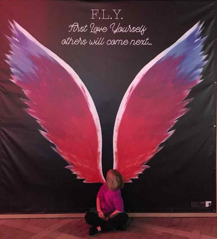 The Ten-Year-Old sits at the base of a giant set of pink wings painted on a wall, so that it looks like the wings are coming out of her back.