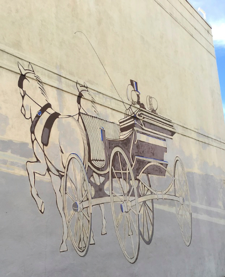 Horse and carriage painted in brown and white on the side of a building in downtown Palo Alto, CA