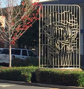 Fred Hunnicutt's aluminum sculpture imitates a face pushed through paper. The so-called paper in this case is actually a grid of aluminum tubes.