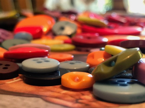 a pile of orange, blue, green, and red buttons on a crafting table