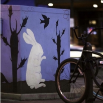 Utility box painted with a blue background on which a white rabbit sits upright, surrounded by birds and cactus plants.