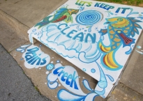 storm drain mural painted on the sidewalk and on the street in front of the drain shows two festive fish playing in the water. The mural reads Let's keep it clean: Drains to Creek